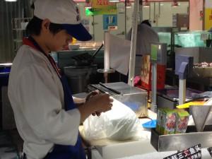 上海蟹を結ぶ店員さん